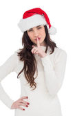 Festive brunette in santa hat keeping a secret — Stok fotoğraf