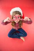 Happy little girl in santa hat holding candy canes — Stockfoto