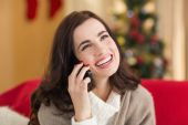Smiling brunette on the phone on christmas day  — Stock Photo