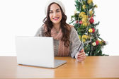 Happy brunette shopping online with laptop — Stock Photo