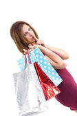 Pretty brunette keeping a secret holding gift bags — Stock Photo
