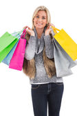 Blonde in winter clothes holding shopping bags — Stock Photo