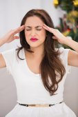 Brunette getting a headache on christmas day — Stock Photo
