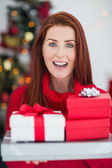 Festive redhead holding pile of gifts — Stock Photo