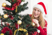 Smiling woman hanging christmas decorations on tree — Stock Photo