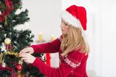 Young woman decorating a Christmas tree — Stock Photo