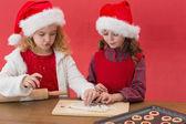 Festive little girls making christmas cookies — Stock Photo