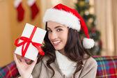 Festive brunette showing gift at christmas — Stock Photo