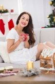 Smiling brunette holding a mug of hot drink — Stock Photo