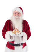 Santa holds a tiny house in his hands — Stock Photo