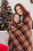 Festive mother and daughter wrapped in blanket — Zdjęcie stockowe