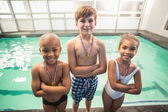 Cute swimming class smiling with medals — Foto de Stock