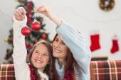 Festive mother and daughter holding baubles — ストック写真