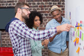 Team looking at sticky notes on wall — Stock Photo