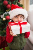 Festive little boy smiling at camera with gift — Stock Photo