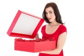 Surprised brunette in red dress opening gift — Стоковое фото