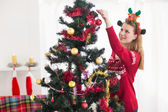 Young woman decorating a Christmas tree — Foto de Stock