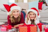 Festive little girl with mother surrounded by gifts — Stock Photo