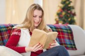Pretty blonde reading book at christmas time — Stock Photo