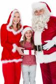 Santa and Mrs Claus smiling at camera with little girl — Stock Photo