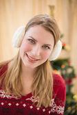Portrait of a smiling blonde wearing earmuffs — Stock Photo
