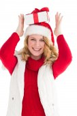 Smiling woman balancing christmas gift on her head — Stock Photo