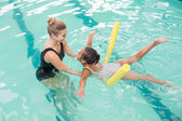 Cute little girl learning to swim with coach — Stock Photo