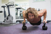 Man doing push ups with kettle bells — Stock Photo