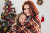 Festive mother and daughter wrapped in blanket — Stockfoto