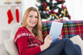 Pretty girl lying on sofa using her tablet smiling at camera — Stock Photo