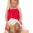 Festive little girl making gingerbread house — Zdjęcie stockowe #57260941