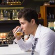 Young man drinking whiskey neat — Stock Photo #57261569