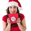 Festive brunette holding gift with bow — Stock Photo #57262111