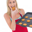 Happy blonde eating hot cookies — Stock Photo #57262135