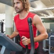 Determined man working out on x-trainer — Stock Photo #57262475