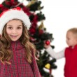 Festive little girl smiling at camera with boy behind — Stock Photo #57262777