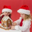 Festive little girls making a gingerbread house — Zdjęcie stockowe #57262793