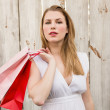 Pretty woman carrying shopping bags over her shoulder — Stock Photo #57263239