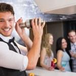 Handsome barman smiling at camera making a cocktail — Stock Photo #57263411