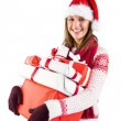 Festive brunette with santa hat holding many gifts — Stock Photo #57265613
