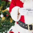 Santa using smartphone with christmas tree behind him — Stock Photo #57265659