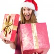 Surprised pretty brunette in santa hat opening gift — Stock Photo #57266519