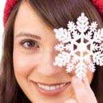 Festive brunette holding snowflake decoration — Stock Photo #57267269