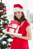 Brunette in red dress holding pile of gift — Stock Photo