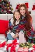 Festive mother and daughter wrapped in blanket — Стоковое фото