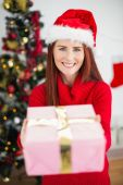 Festive redhead holding christmas gift — Stock Photo