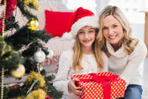 Festive mother and daughter beside christmas tree — Stockfoto
