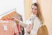 Pretty blonde looking at clothes on rail — Stok fotoğraf