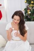 Brunette holding mug with marshmallow at christmas — Stock Photo