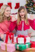 Festive mother and daughter with many gifts — Stock Photo
